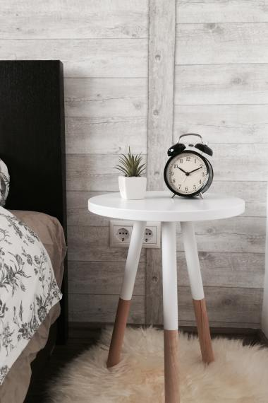 bedside table with flowers and an alarm clock