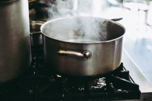 A stainless steel pan with boing water on the stove.