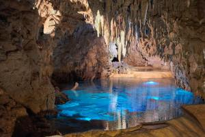 a cave with a beautiful blue lake and stalactites hanging from the ceiling.