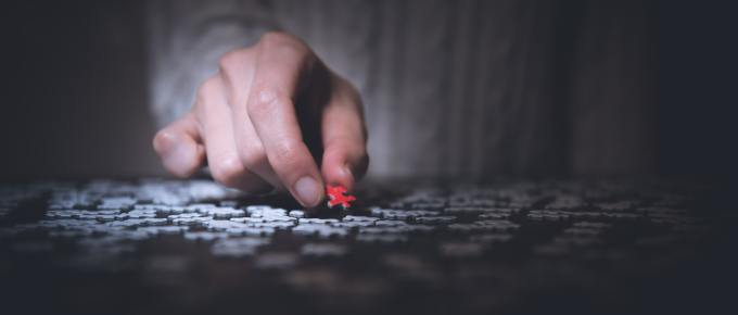 a young child putting a puzzle piece on a puzzle