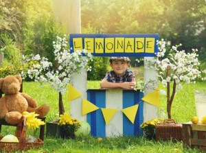 a little boy has an outdoor homemade lemonade stand with a sign and he looks happy for a small business or money concept