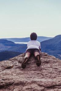 a woman laying on her stomach on a mountaintop