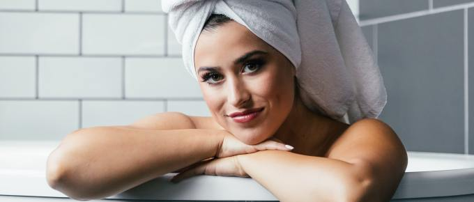 a beautiful woman in a bathtub with a towel on her head