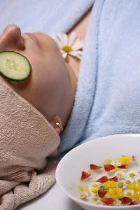 a woman at a spa with a cucumber slice over her eye