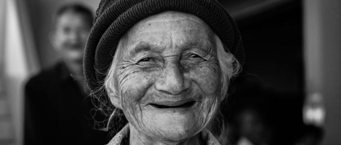 a smilng old woman wearing a black hat