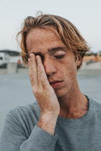 a young man with his hand on his face in stress