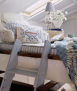 Moving up — Janice turned the crawl space above the living room into a cozy and intimate sleeping loft simply by creating a platform to hold a cushy mattress and pillows. A basket plays double duty as storage/bedside table.