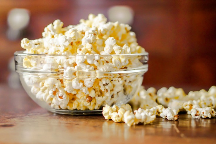 Closeup Popcorn in a glass cup on a wooden table and blurry background.