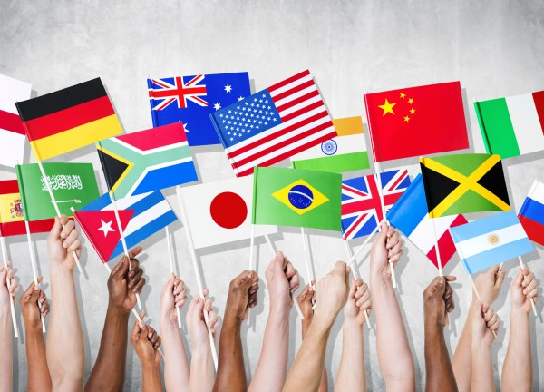Group of hands holding national flags.