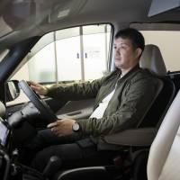 Yusuke Goto senta-se em uma minivan Serena em uma concessionária Nissan Motor em abril. Tendo evitado um acidente com o Toyota Crown equipado com funções de piloto automático há cinco anos, Goto diz que foi uma escolha fácil para a Serena, promovendo características semelhantes para um preço muito mais barato. | BLOOMBERG