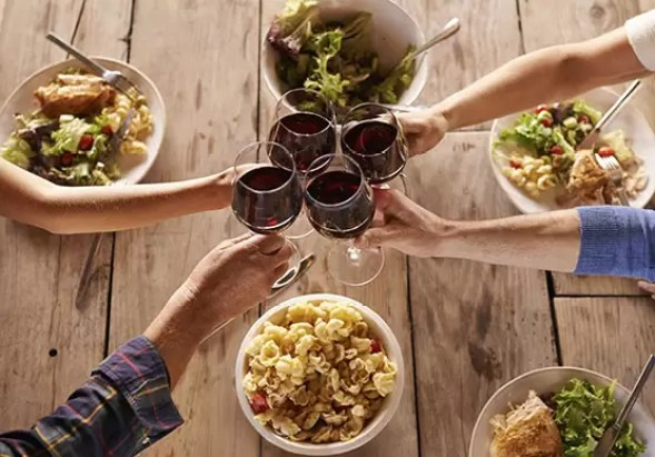 Shot of people toasting with wine over a meal