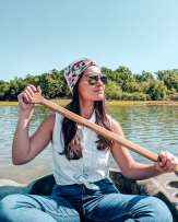 Girl on fishing boat with paddle
