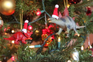 2 dinosaur ornaments hanging in a tree