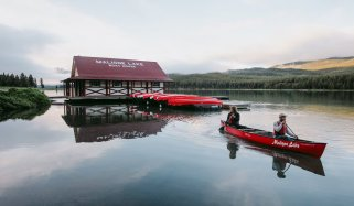 View of Maligne Lake Boat House and couple paddling in a red, rental canoe at Jasper National Park.
