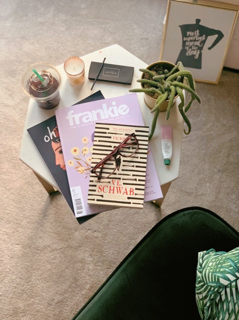 Side table with book, glasses, cactus, candle, matches, iced coffee