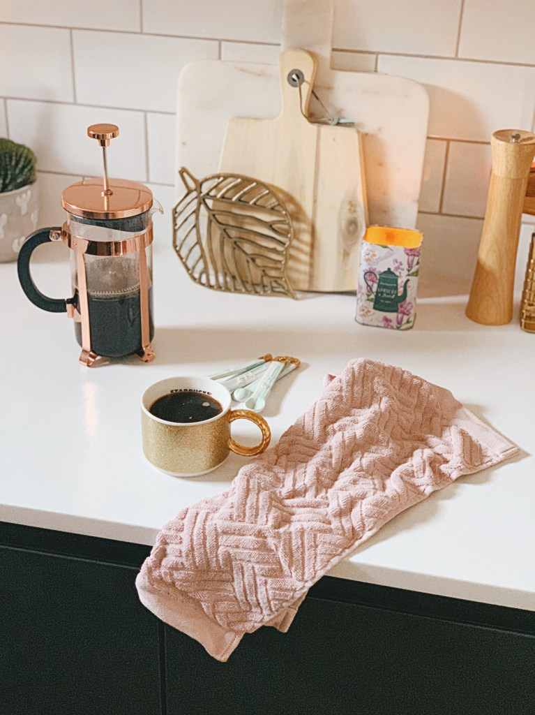 copper cafetiere coffee gold mug kitchen subway tiles pink tea towel chopping boards candle