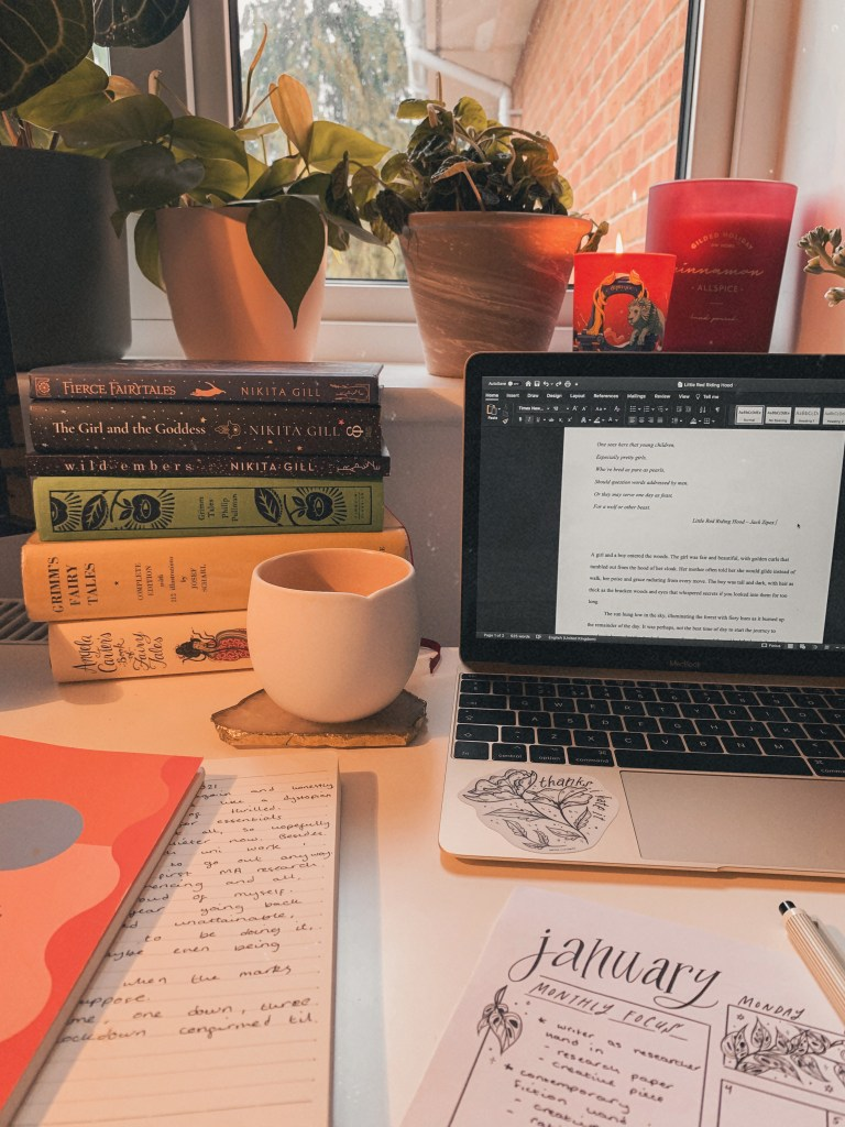 A word document is shown on an open laptop, sat on a desk covered in papers. There is a stack of fairytale books in the background as well as a burning candle, and a white coffee mug on a quartz coaster.