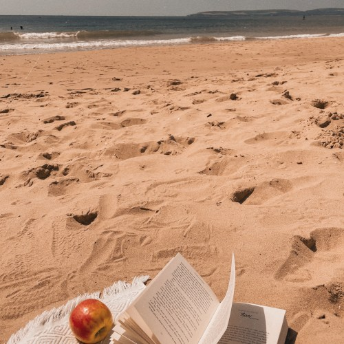 view of the beach, sand in the foreground and sea in the background. The corner of a beach towel is visible with an open book and an apple on it