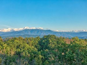 Above it All is a luxury three bedroom cabin in Pigeon Forge with an amazing mountain view, theater room, private unobstructed view, fire pit, and luxury furnishings
