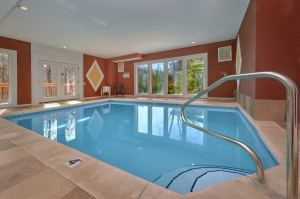 Pool Movie 1 is a 6 bedroom rental cabin in Maranatha Resort featuring a large indoor pool, theater room, and other amazing features