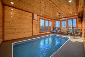 Top of the World Pool Lodge is a luxury three bedroom cabin in Pigeon Forge with an indoor pool, mountain view, theater room, and theater in the pool room