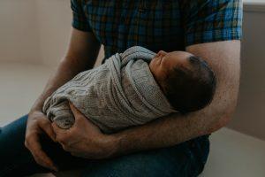 Swaddled newborn with parent