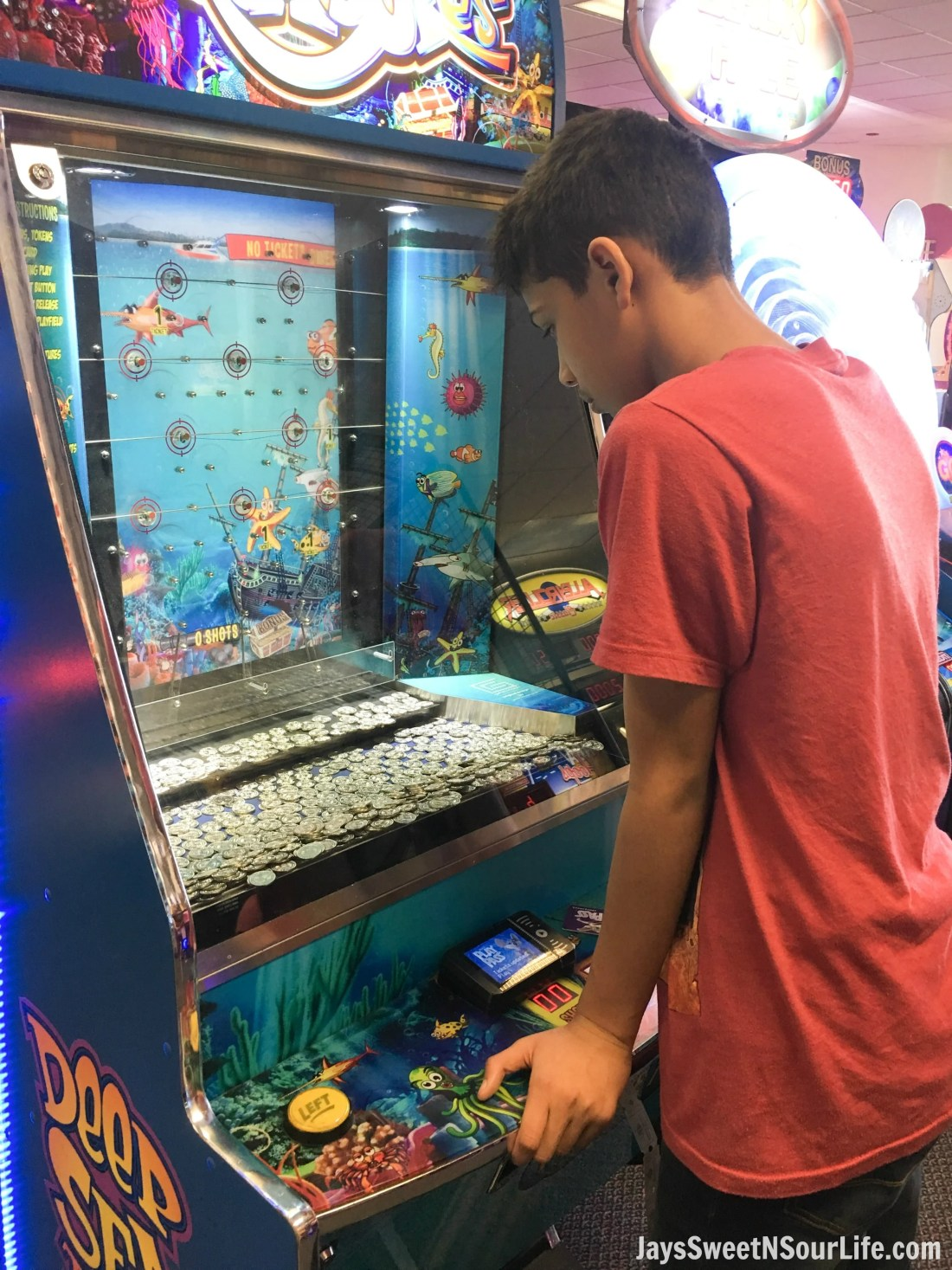 Chuck e cheeses VIP birthday party offers 2 hour of unlimited game play. African american boy playing fish coin game and winning tickets.
