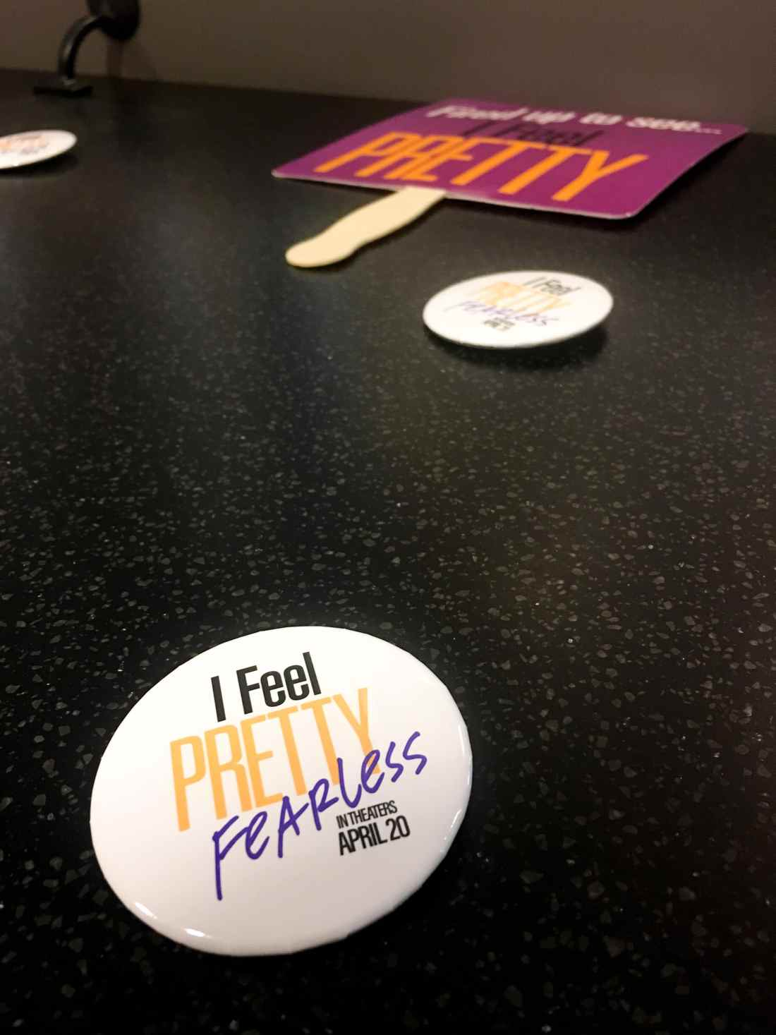 I Feel Pretty Fearless Button on table. The I Feel Pretty Film is in theaters everywhere today.