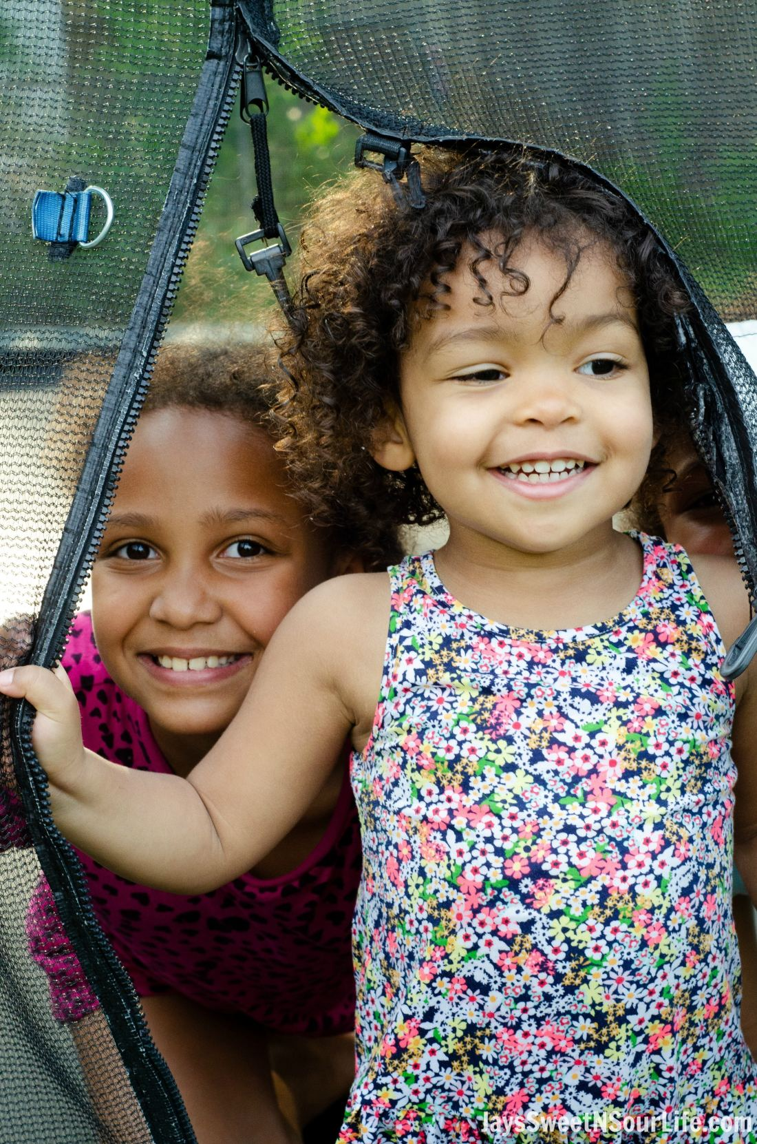 Litte african american girls smiling on a trampoline. Guests of a Beach Sundae Party.