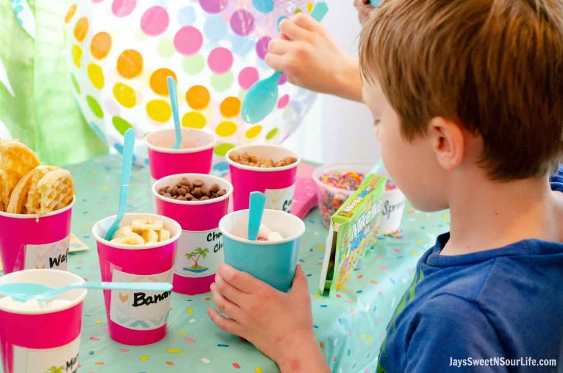 Little boy creating his own sundae at the Beach Sundae Party Table. Add your favorite toppings and then enjoy your fun creation.