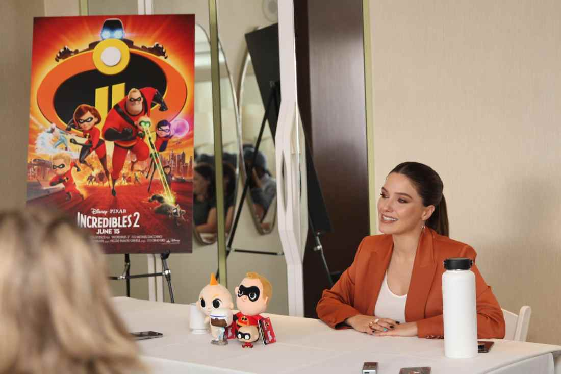Incredibles 2 Interview with Sophia Bush Voice of Voyd Sitting next to Incredibles 2 Movie Poster. Disney Pixars Incredibles 2 film is in theaters everywhere today.