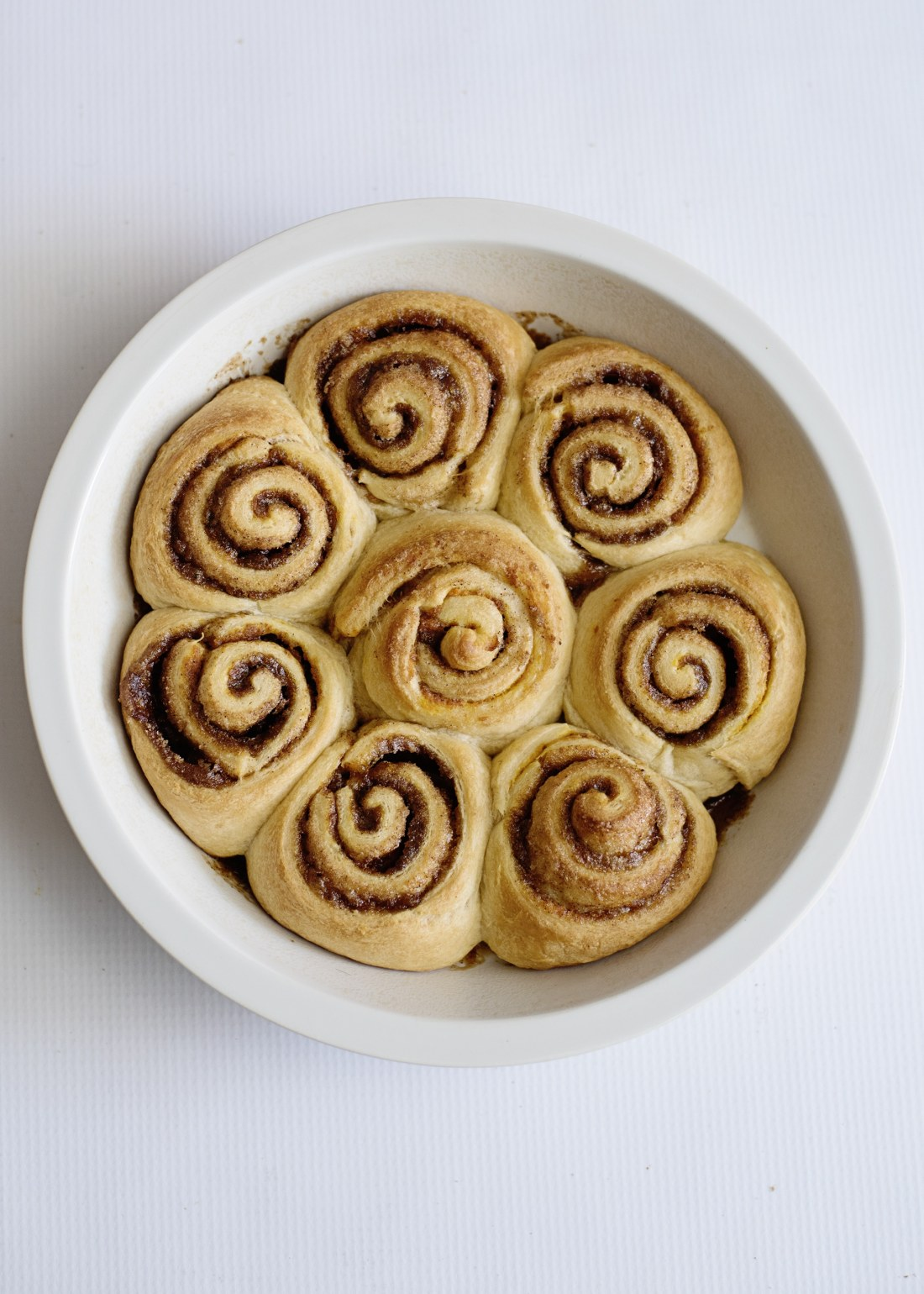 Pumpkin Spice Cinnamon Rolls Baked In Pan. Fill your home with the delicious smell of these easy to make Pumpkin Spice Cinnamon Rolls.