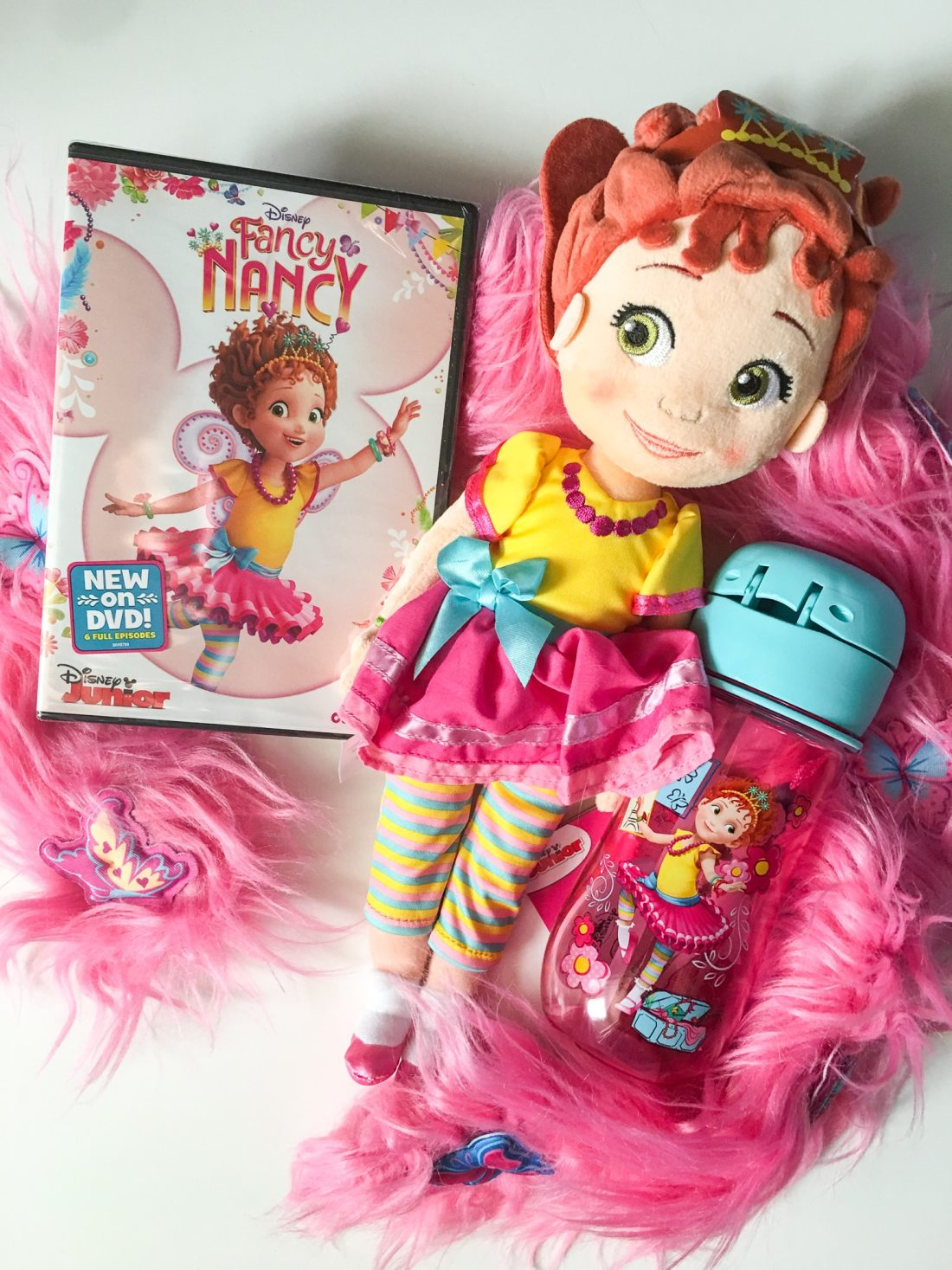 """Fancy Nancy DVD Plush Toy and Canteen. Grab some glitter, add a dash of """"ooh la la,"""" sprinkle in original songs and Voilà! Get set to pour on the fun with Fancy Nancy in her newest DVD from Disney Junior."""