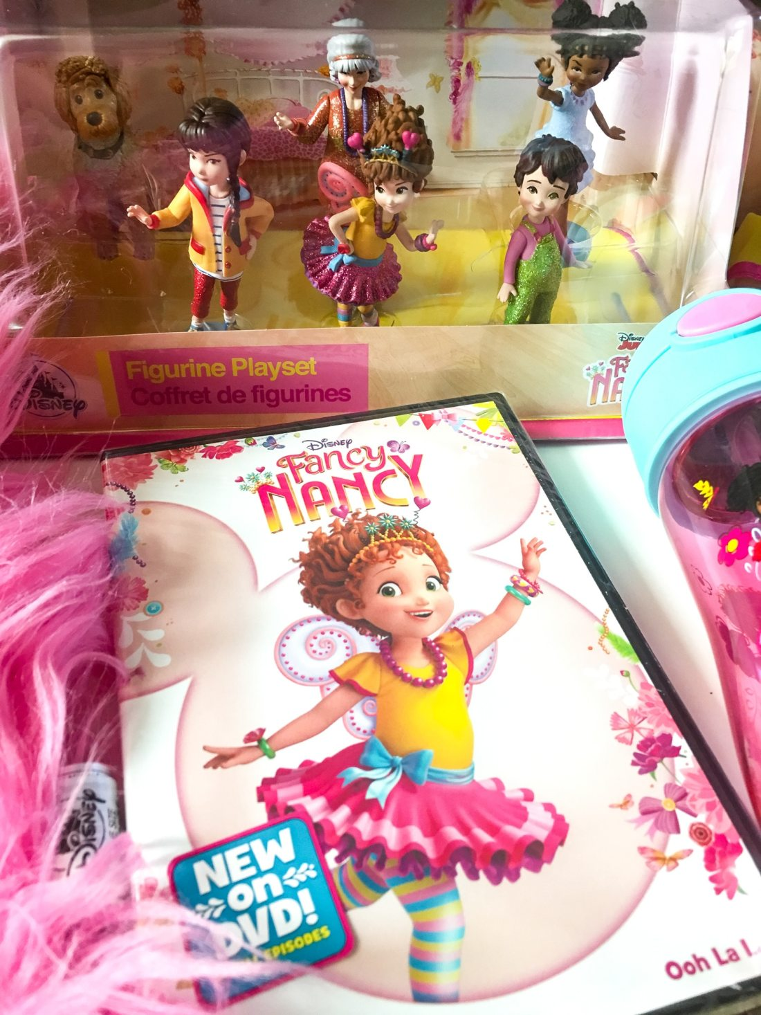 "Disney Junior Fancy Nancy DVD and Figure Set. Grab some glitter, add a dash of ""ooh la la,"" sprinkle in original songs and Voilà! Get set to pour on the fun with Fancy Nancy in her newest DVD from Disney Junior."