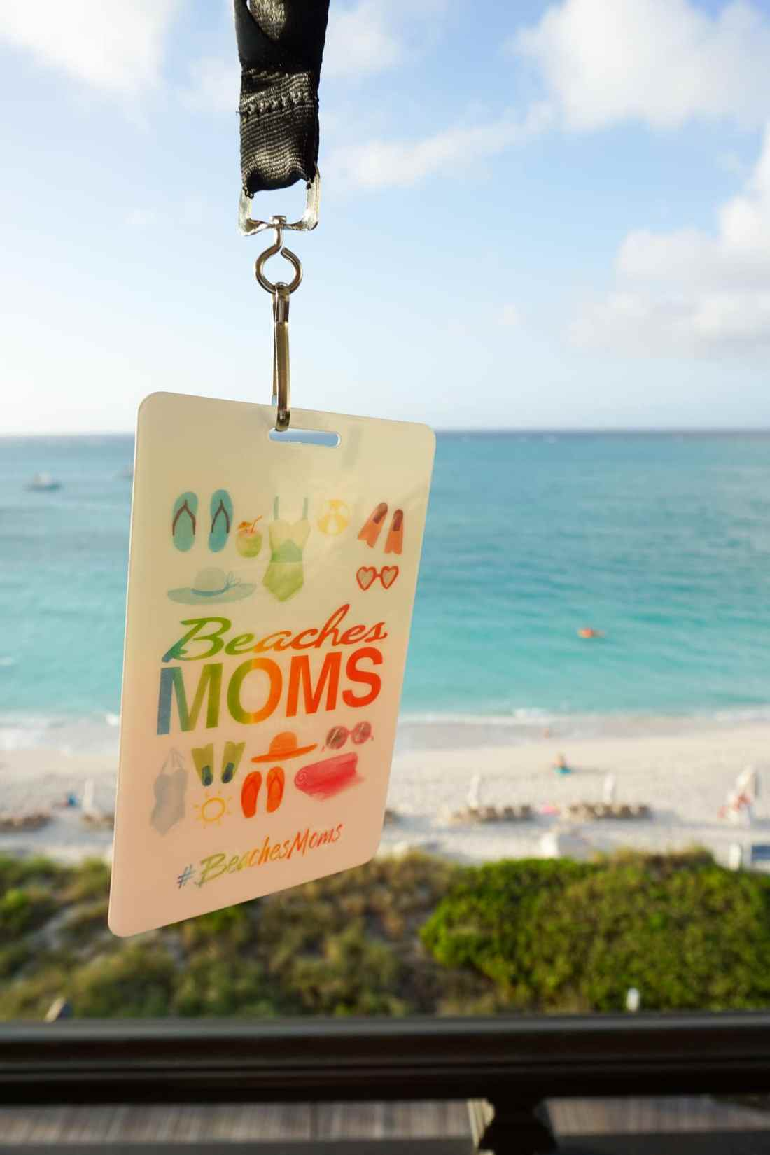 2018 Beaches Moms Badge in front of the ocean at Beaches Resorts in Turks and Caicos. Read all about my international adventure with my family on my blog now.