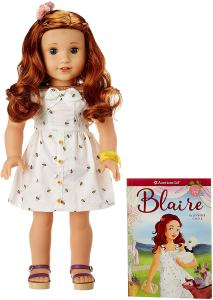 "American Girl Doll Blaire. Meet Blaire, the 2019 Girl of the Year! She's a chef-in-training, party planner, and chicken wrangler at her family's farm and restaurant. The 18"" Blaire doll has bright green eyes that open and close, and curly red hair. She has a huggable cloth body, and her movable head and limbs are made of smooth vinyl. She comes with the Blaire paperback book, plus her signature outfit:"