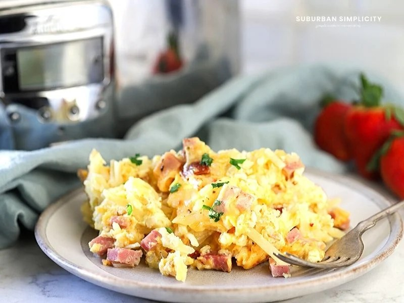 This easy Overnight Christmas Crock-Pot Breakfast Casserole is a delicious crowd-pleaser! Shredded potatoes are layered between savory ham, cheese, and eggs. A classic crockpot breakfast guests will rave about!