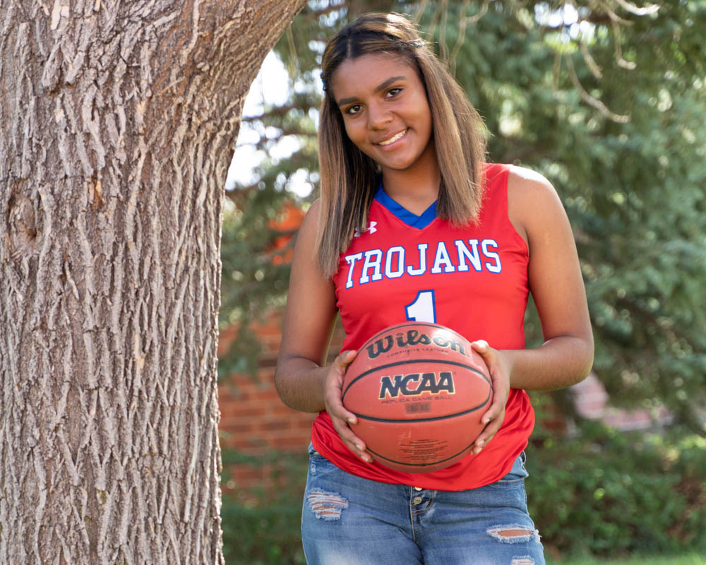 African American female high school student posing in her team jersey with a basketball