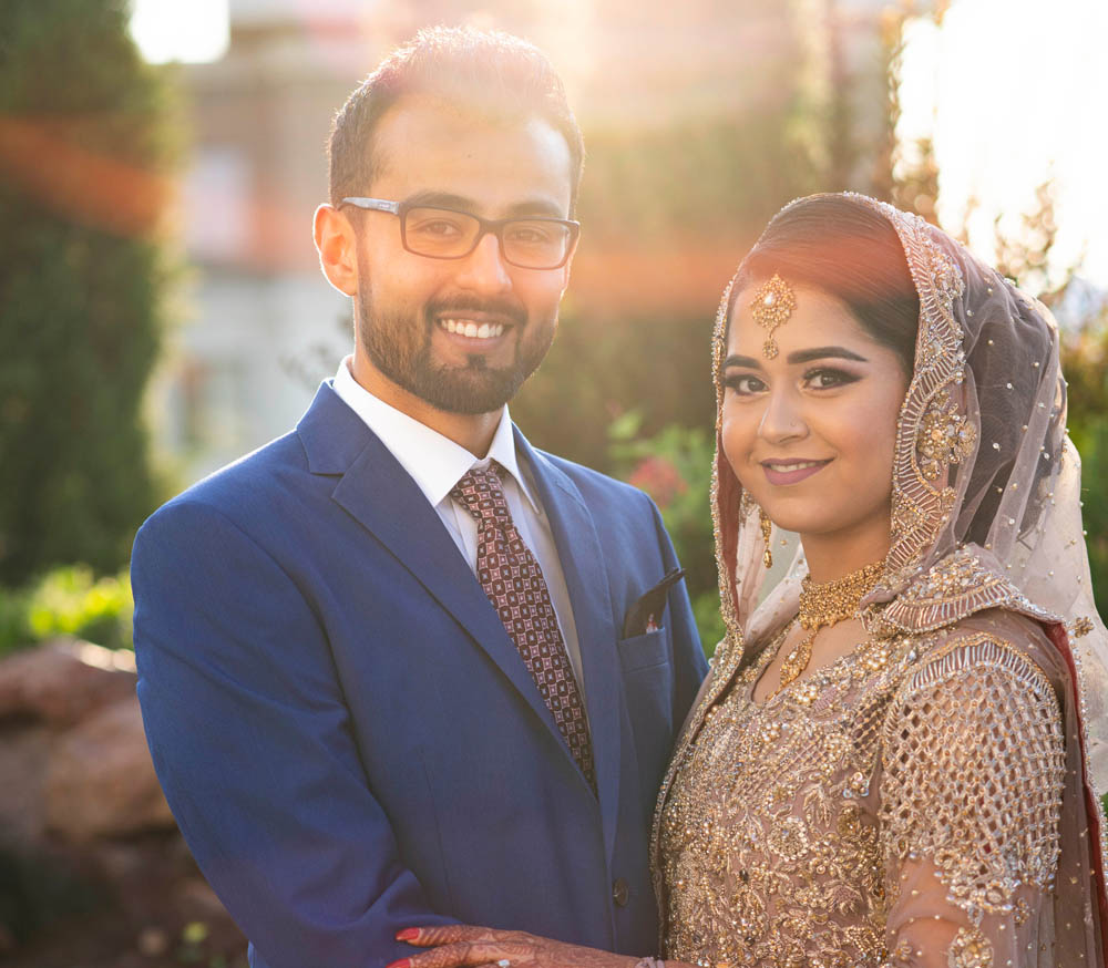 Pakistani couple posing at wedding venue in front of bright sun just after their ceremony