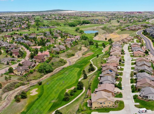 Aerial drone photograph of a property near a golf course