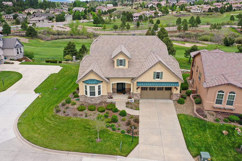 Drone shot of a house in an expensive neighborhood with a golf course