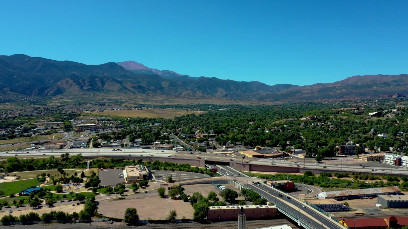 Aerial video of downtown Colorado Springs, medium traffic on I-25, sunny day, Pikes Peak in view