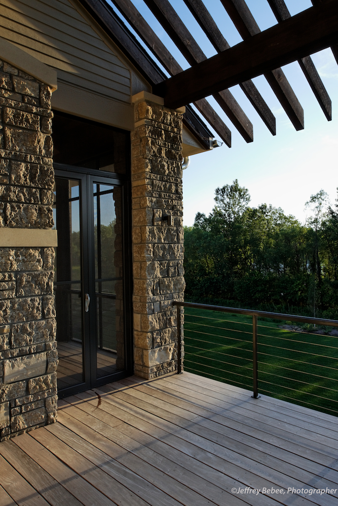 Back deck entrance to screened in porch, exposed rafter tails and stone work.