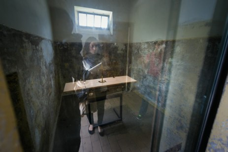 reflective in front of a prison cell in the concentration camp Dachau an imprisoned priest did pray in this cell with other prisoners