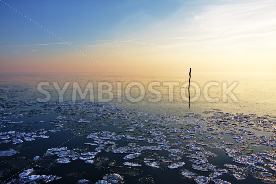 Fishing net stick in calm frozen water - Jan Brons Stock Images