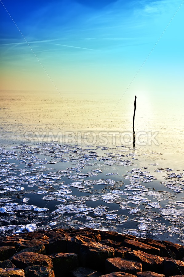 Sun going down in calm frozen lake - Jan Brons Stock Images