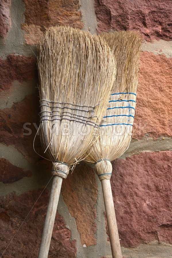 Straw brooms in love - Jan Brons Stock Images