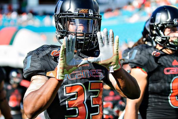 "Mitch Davis flashes the ""U"" as he walks onto the field"