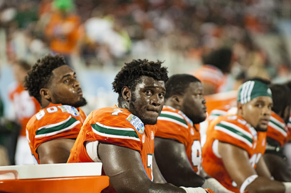 Kendrick Norton, Miami Hurricanes DL, takes a seat on the bench as the Hurricanes offense takes the field