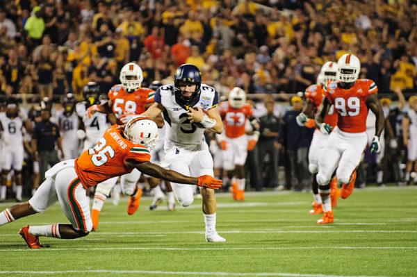 West Virginia QB, Skyler Howard, tries to rush past the Hurricanes defense